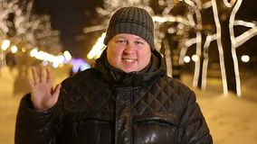 Portrait of happy man greeting outdoors during cold winter evening.  stock footage
