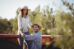 Portrait of happy man holding girlfriend standing on tractor Stock Image