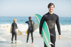Portrait of happy man holding a surfboard on the beach Royalty Free Stock Photo