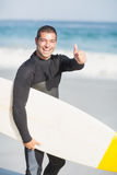 Portrait of happy man holding a surfboard on the beach. On a sunny day Stock Photos