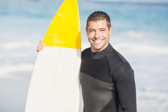 Portrait of happy man holding a surfboard on the beach Royalty Free Stock Images