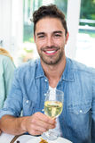 Portrait of happy man holding white wine glass Stock Photo