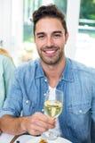 Portrait of happy man holding white wine glass Stock Photo