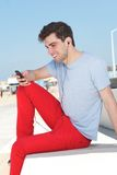 Portrait of a happy man listening and looking at mobile phone outdoors Stock Photo