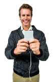 Portrait of happy man listening music while using mobile phone. Against white background royalty free stock photo