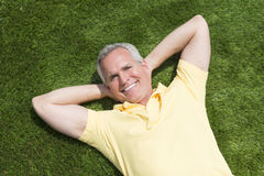 Portrait Of Happy Man Lying On Grass Stock Images