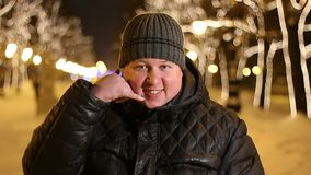 Portrait of happy man making a gesture `call me` with his fingers outdoors during cold winter night. Portrait of happy man making a gesture call me with his stock video footage