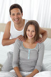 Portrait of a happy man massaging his girlfriend. On the bed at home stock photo