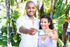 Portrait of happy man with pregnant wife holding sonogram Stock Images