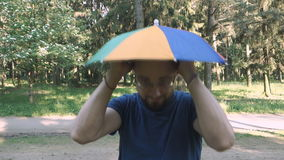 Portrait of happy man with rainbow hat umbrella on head stock video