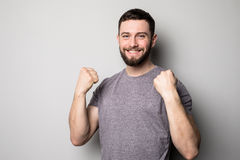 Portrait of happy man rise up hands and successful achievement of goals on grey. Portrait of happy man rise up hands and successful achievement of goals Royalty Free Stock Photography