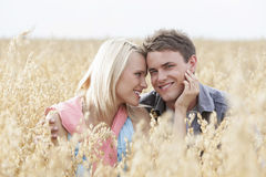 Portrait of happy man sitting with romantic woman amidst field Stock Images