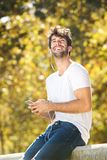 Happy man sitting on wall in park with cellphone Stock Photography