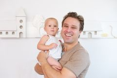 Portrait of a happy man smiling and holding cute baby Royalty Free Stock Image