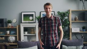 Portrait of happy man smiling and laughing expressing surprise, happiness and positive emotions standing at home alone. Portrait of happy young man smiling and stock video footage