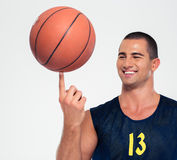 Portrait of a happy man spinning basketball ball. Isolated on a white background Royalty Free Stock Image