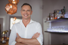 Portrait of happy man standing with arms crossed. In restaurant Stock Image