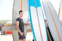 Portrait of a happy man standing at beach with surfboard Royalty Free Stock Photo