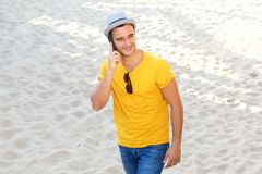 Happy man talking on cellphone at the beach. Portrait of happy man talking on cellphone at the beach royalty free stock photo