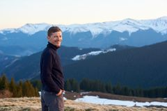 Male tourist enjoying beautiful panorama in the evening. Portrait of happy man tourist in the evening. On the background beautiful panorama of snow-covered Stock Images