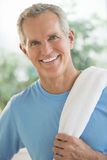 Portrait Of Happy Man With Towel On Shoulder. Portrait of happy mature man with towel on shoulder standing outdoors Royalty Free Stock Photography