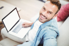 Portrait of happy man using laptop on sofa Royalty Free Stock Images