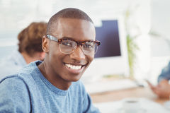 Portrait of happy man wearing eyeglasses while sitting at desk. In office Stock Photos