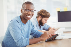 Portrait of happy man wearing eyeglasses while using digital tablet Royalty Free Stock Photography
