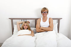 Portrait of happy man wearing retro glasses while sitting with woman in bed Stock Images