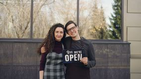 Portrait of happy married couple business partners opening cafe and holding `we are open` board in front of window stock video
