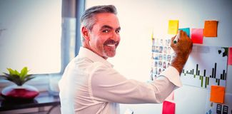 Happy mature businessman making strategies on whiteboard in creative office stock photo