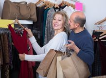 Mature couple choosing apparel in store. Portrait of happy mature couple choosing new apparel in the store Royalty Free Stock Photography