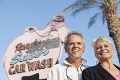 Portrait of a happy mature couple in front of car wash signboard Royalty Free Stock Images