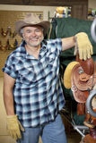 Portrait of a happy mature cowboy standing by saddle in feed store Stock Image