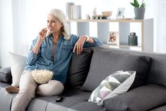 Glad senior woman watching tv at home. Portrait of happy mature lady eating popcorn while viewing television show. She is relaxing on couch and laughing. Copy Royalty Free Stock Photography