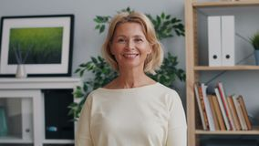Portrait of happy mature lady looking at camera and smiling standing in office