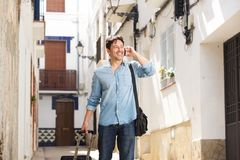 Happy mature male traveler walking on the street using mobile phone. Portrait of happy mature male traveler walking on the street using mobile phone Stock Photos
