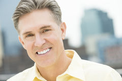 Portrait Of Happy Mature Man. Close-up portrait of happy mature man with buildings in background Royalty Free Stock Image