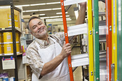 Portrait of a happy mature man with ladder in hardware store Stock Photo