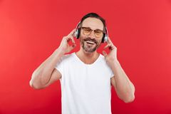 Portrait of a happy mature man listening to music. With headphones over red background stock photo