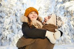Father and Daughter in Winter Park. Portrait of happy mature men playing with little girl in winter forest, copy space royalty free stock image