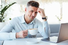 Portrait of a happy mature man using laptop computer. While sitting at the cafe table and drinking coffee indoors Stock Images