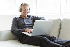 Portrait of happy mature man using laptop lying on sofa in house royalty free stock photos
