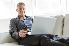 Portrait of happy mature man using laptop lying on sofa in house stock photos