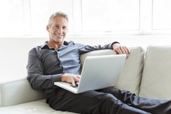 Portrait of happy mature man using laptop lying on sofa in house royalty free stock photography