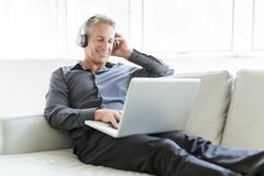 Portrait of happy mature man using laptop lying on sofa in house royalty free stock photo