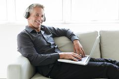 Portrait of happy mature man using laptop lying on sofa in house stock images