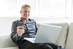 Portrait of happy mature man using laptop lying on sofa in house. A Portrait of happy mature man using laptop lying on sofa in house Stock Photo