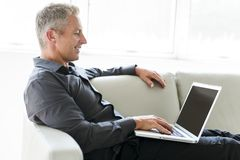 Portrait of happy mature man using laptop lying on sofa in house. A Portrait of happy mature man using laptop lying on sofa in house Royalty Free Stock Photography