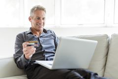 Portrait of happy mature man using laptop lying on sofa in house. A Portrait of happy mature man using laptop lying on sofa in house Stock Images